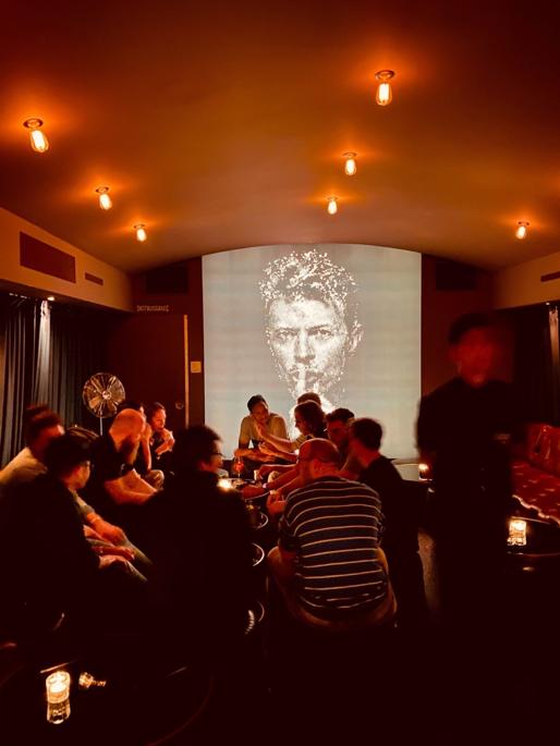 Das TBO Team sitzt beim Afterwork. Im Hintergrund leuchtet ein David Bowie Bild groß an der Wand.