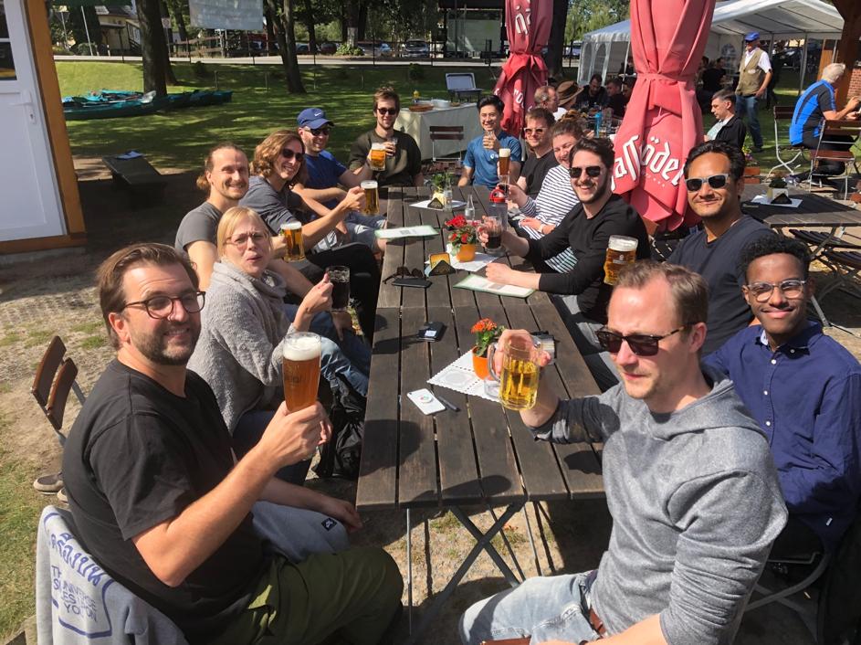 Das TBO-Team sitzt am Tisch im Spreewald beim Grillen und stößt mit Bier an